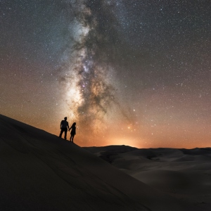 A couple holds hands under the Milky Way Galaxy